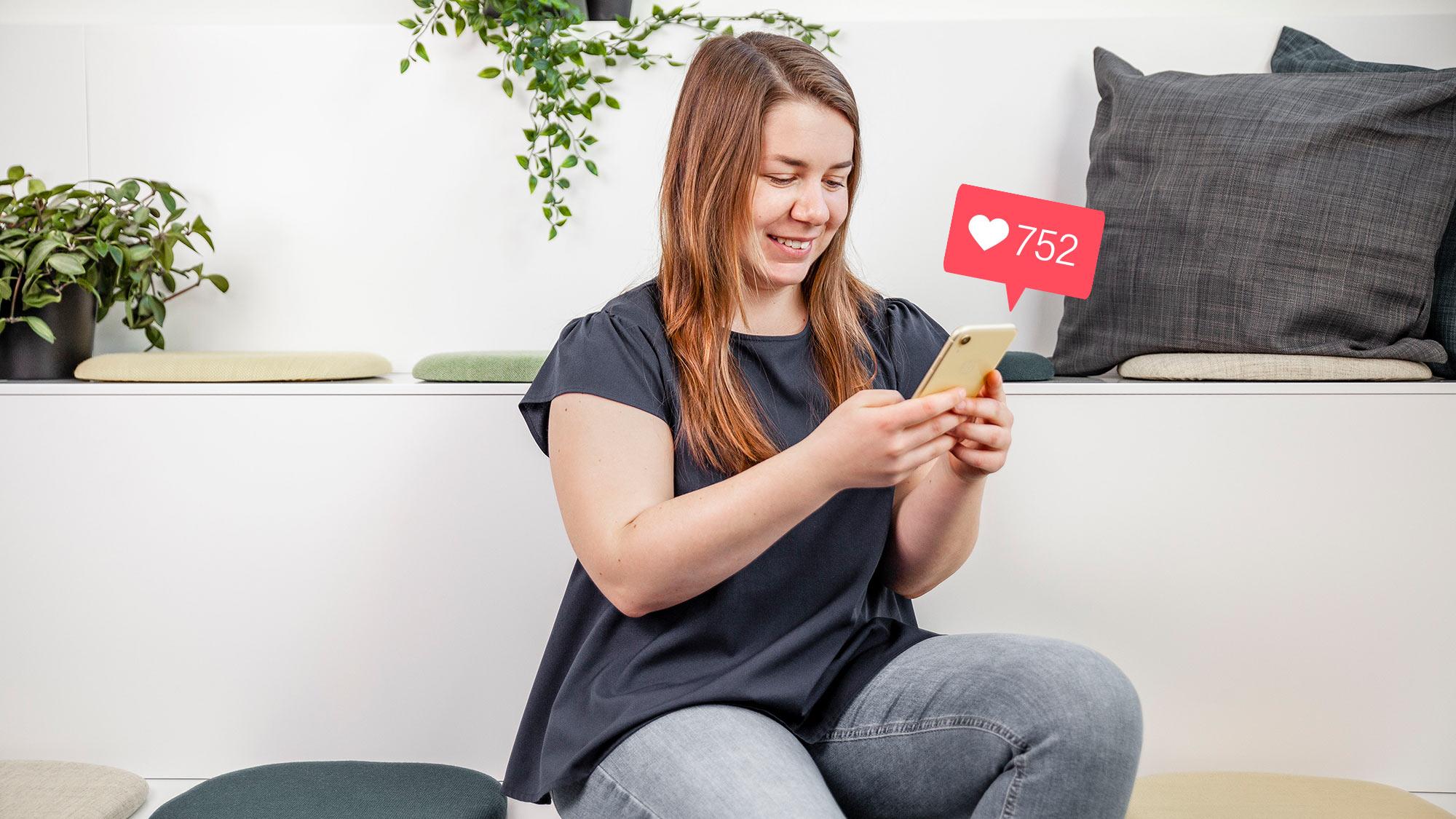 Angelica Bengtsson sitter med en mobil i handen och en icon visar att hon fått likes på Instagram.