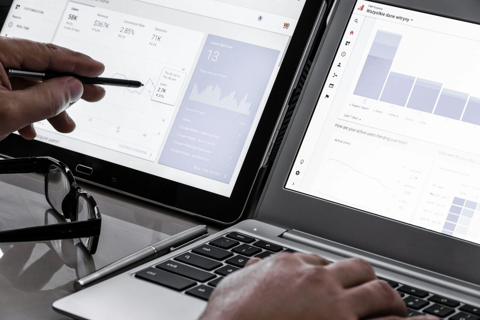 Händer på ett skrivbord med dubbla skärmar som visar Google Analytics