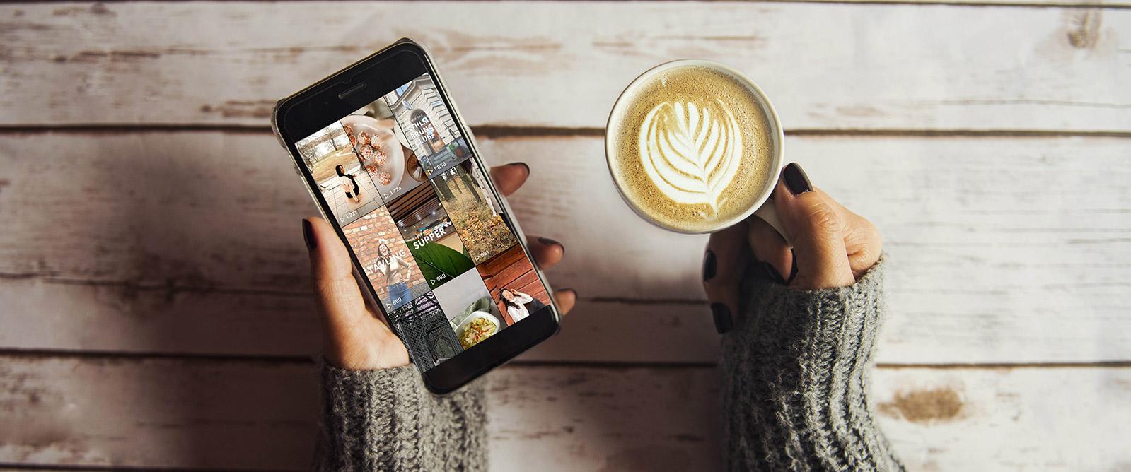 En kvinnas händer håller i en kaffekopp och en mobil med Reels öppen