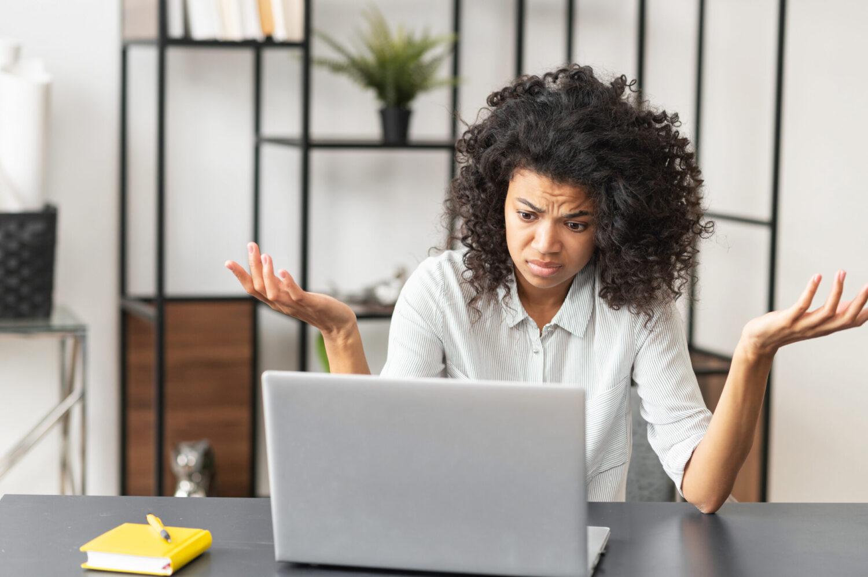 förvirrad kvinna framför datorn