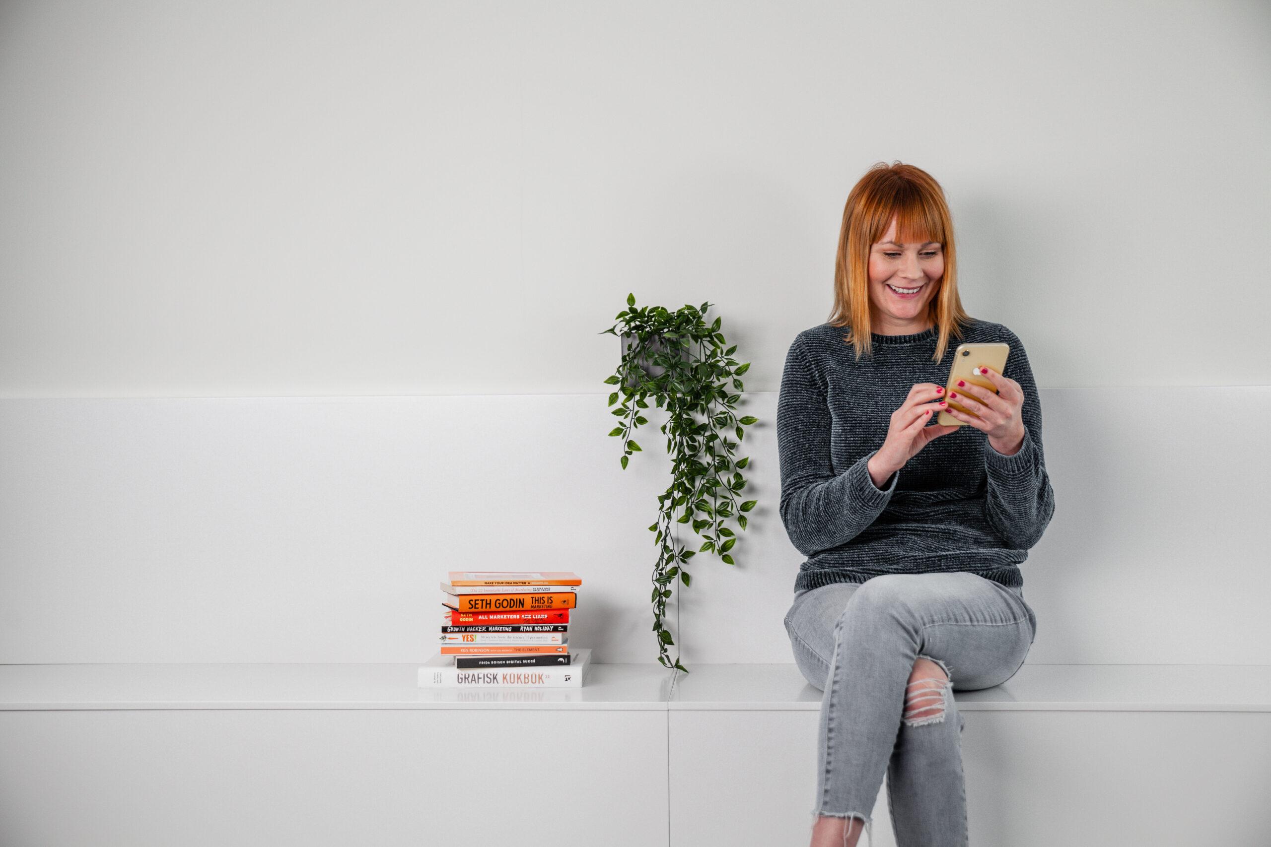 ung kvinna på vit bänk inomhus som tittar ner i sin telefon och ler